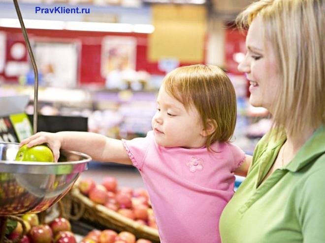 Мама с ребенком покупают фрукты