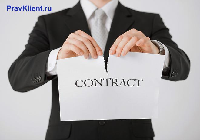 Мужчина в деловом костюме разрывает контракт