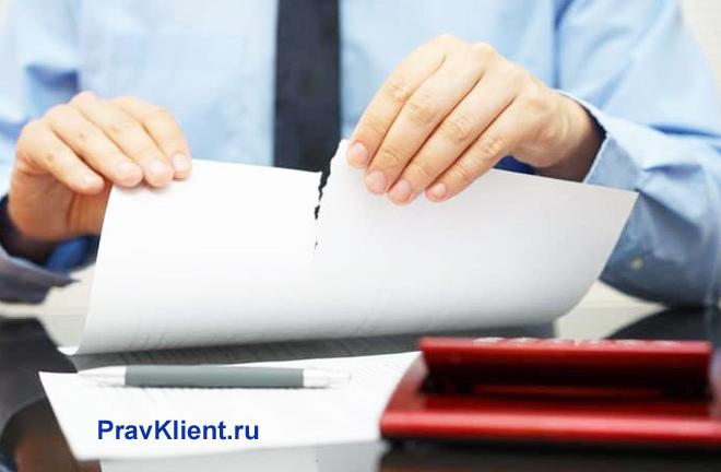 Бизнесмен разрывает лист бумаги пополам