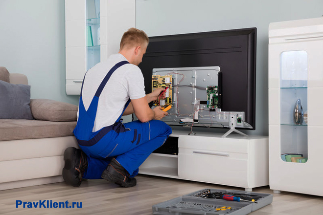 Мужчина производит ремонт телевизора