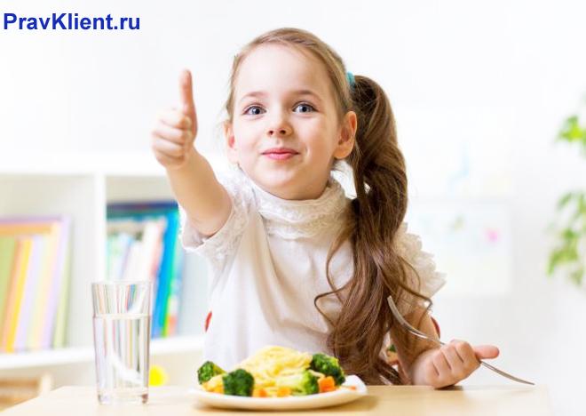Девочка ест здоровую пищу и показывает класс