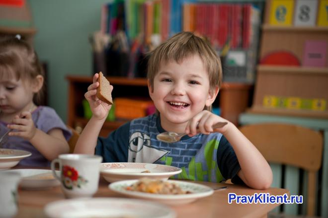 Мальчик ест суп в детском саду