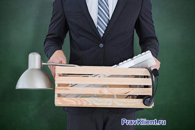 Бизнесмен несет в деревянной коробке вещей