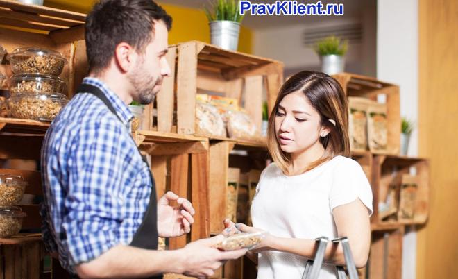 Девушке показывает продукцию мужчина в клетчатой рубашке