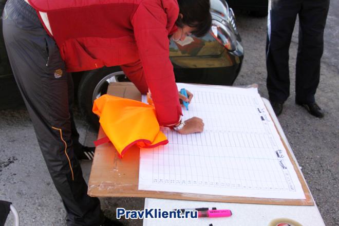 Девушка ставит свою подпись в документе