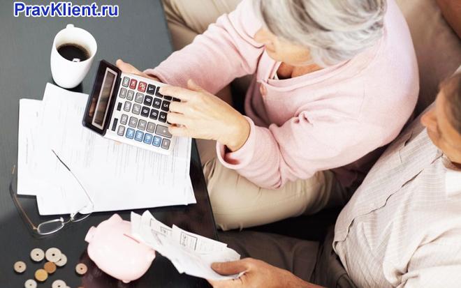 Семейная пара считает на калькуляторе за столом