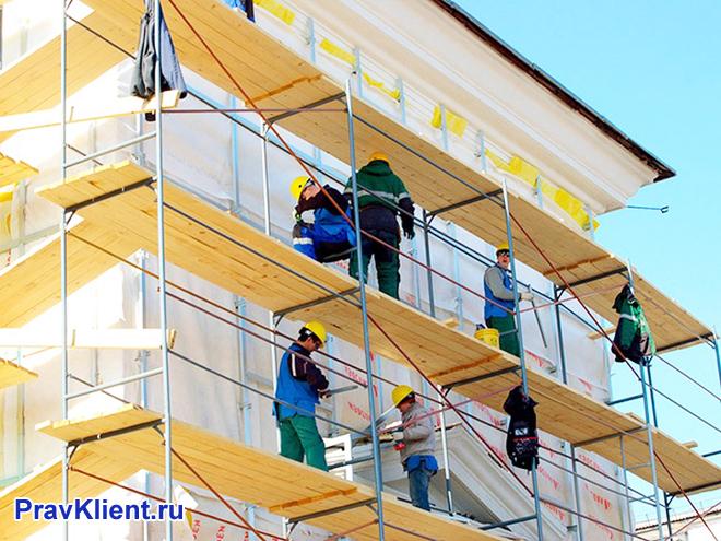 Рабочие работают на строительных лесах