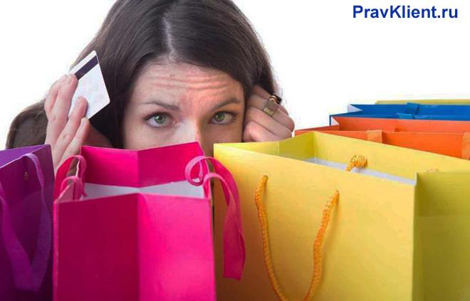 Девушка держит в руке карточку, рядом стоят разноцветные пакеты