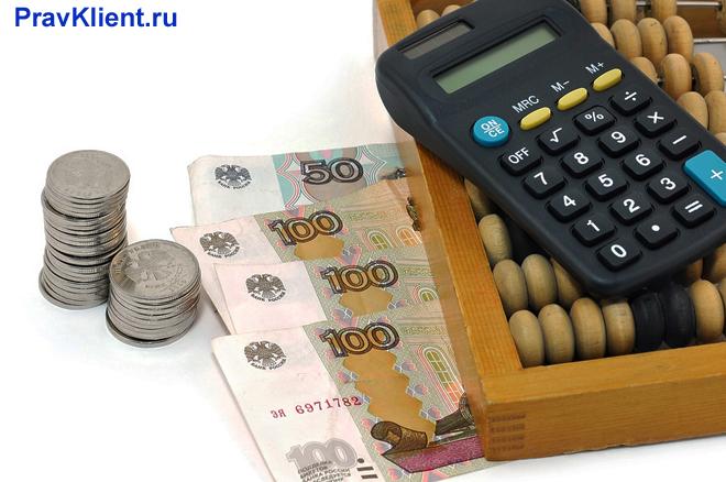 Калькулятор лежит на счетах, рядом лежат деньги