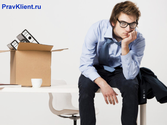 Грустный мужчина сидит на работе с собранными вещами