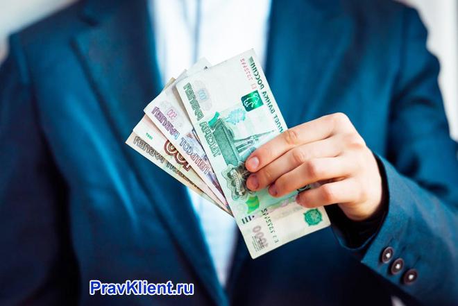Бизнесмен держит в руке деньги