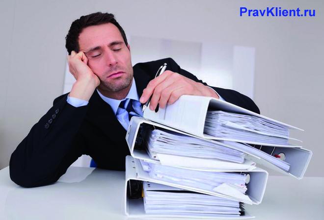 Мужчина задремал на работе с папками документов