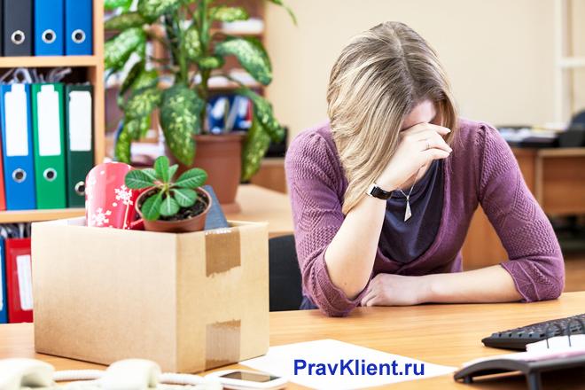 Расстроенная женщина сидит за своим рабочим местом, рядом стоит коробка с ее вещами
