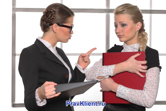 Девушка стоит с красной папкой, с ней разговаривает начальница