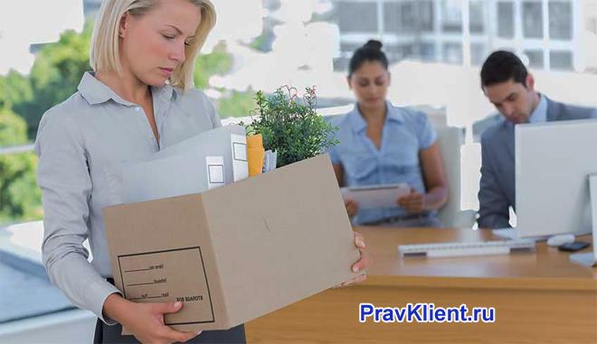 Девушка несет в руках коробку с вещами на фоне ее коллеги