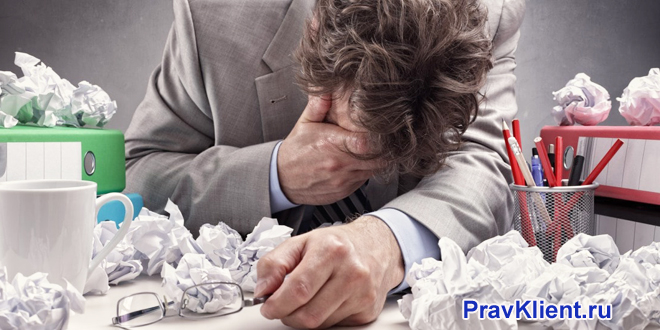 Расстроенный офисный работник, смятая бумага