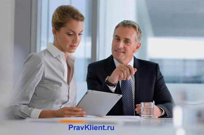 Сотрудница и ее начальник читают документы в офисе