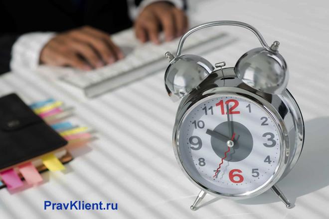 Бизнесмен сидит за столом, на переднем фоне стоит будильник
