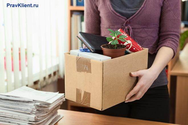 Девушка стоит рядом с письменным столом и держит в руках коробку с личными вещами