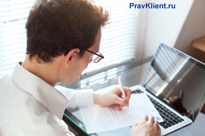 Бизнесмен пишет на листке бумаги, которой лежит на клавиатуре ноутбука