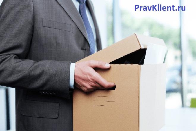 Мужчина в деловом костюме несет картонную коробку в руках