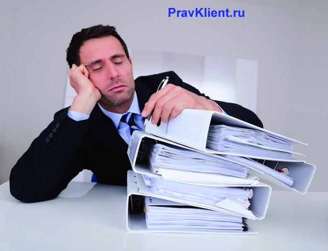 Офисный работник спит на рабочем месте