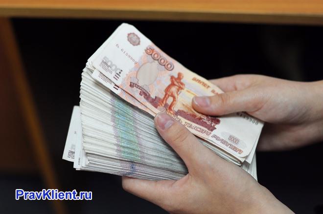 Человек держит в руках деньги
