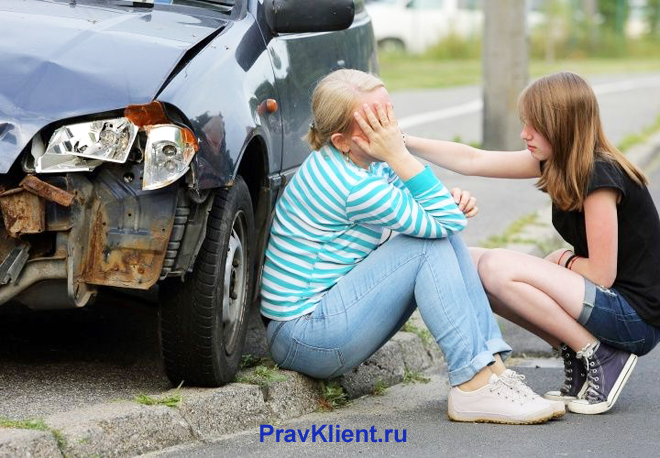 Девушку успокаивают рядом с разбитой машиной