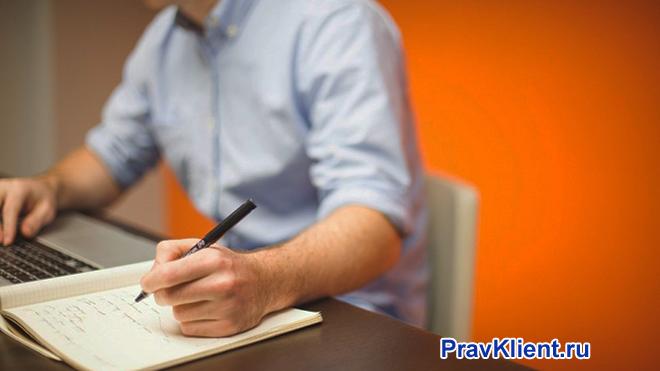 Мужчина делает записи в тетради