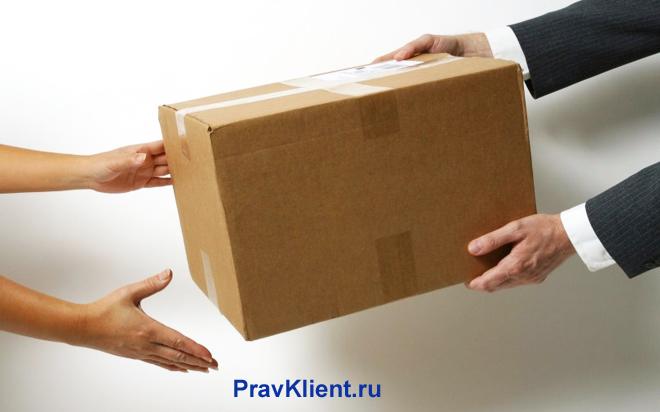 Передача картонной коробки с товаром их рук в руки