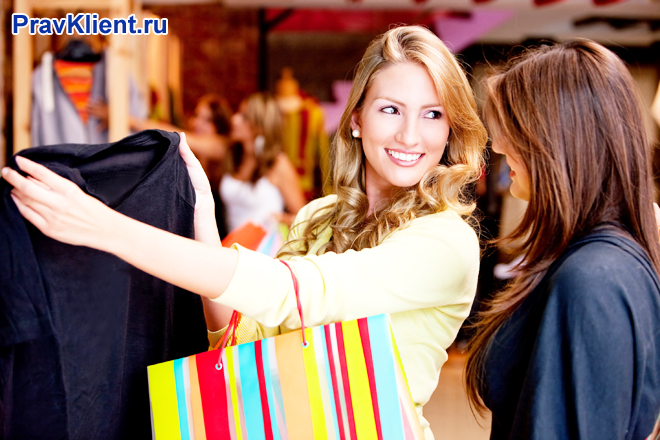 Подруги рассматривают вещи в магазине одежды