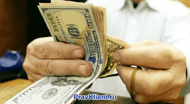Мужчина пересчитывает в руках доллары