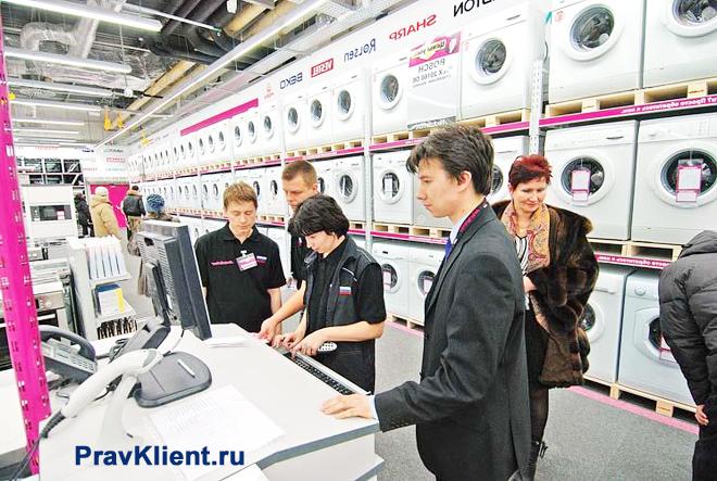 Покупатели выбирают стиральную машинку