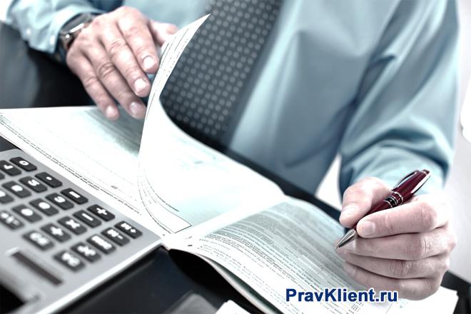 Мужчина переворачивает листок тетради, рядом лежит калькулятор