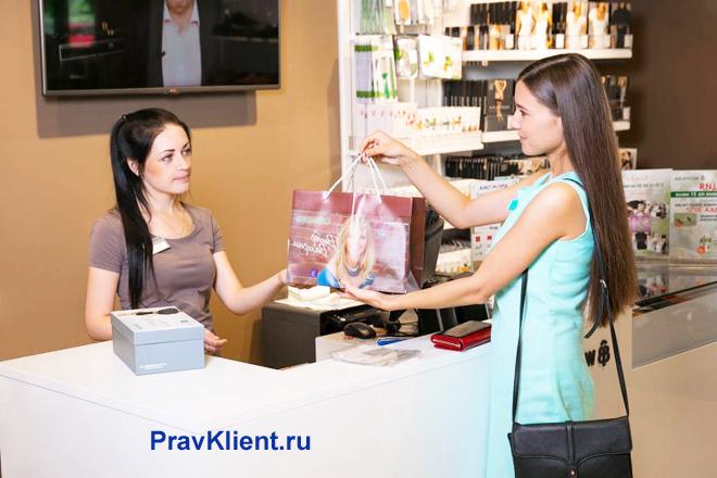 Девушка возвращает пакет с покупкой на кассу
