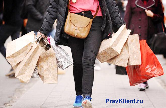 Девушка идет по улице со множеством покупок