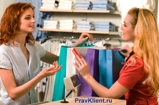 Девушка расплачивается на кассе картой за покупки