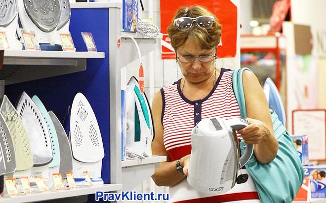 Женщина выбирает электрический чайник в магазине