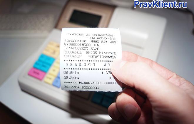 Продавец держит в руке фискальный чек, рядом стоит касса