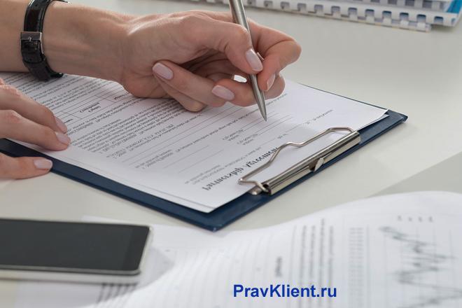 Девушка подписывает документы за своим рабочим столом