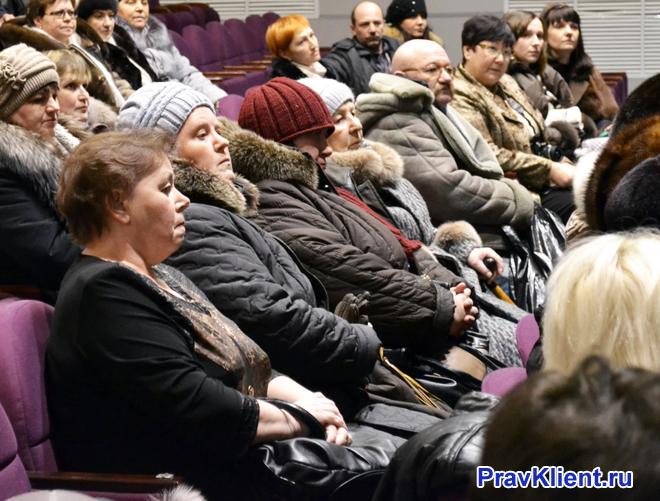 Люди в верхней одежде сидят на креслах в актовом зале