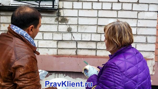 Женщина и мужчина фиксируют трещину на фасаде дома