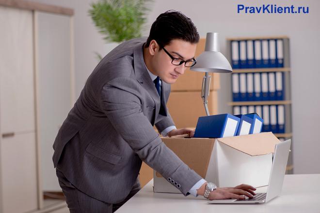 Мужчина покидает после работы свой кабинет, выключает компьютер