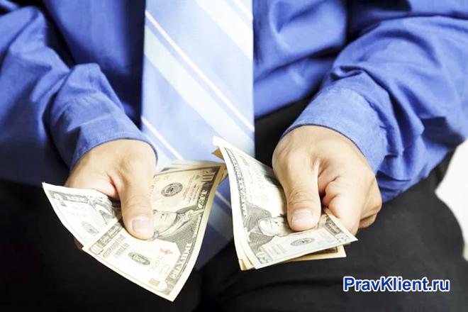 Мужчина пересчитывает деньги в руках