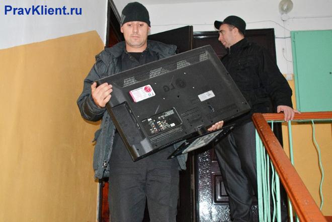 Мужчина выносит из квартиры телевизор