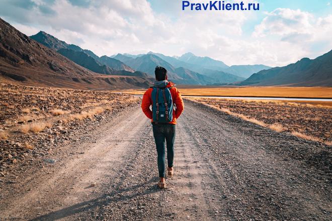 Путешественник идет по дороге