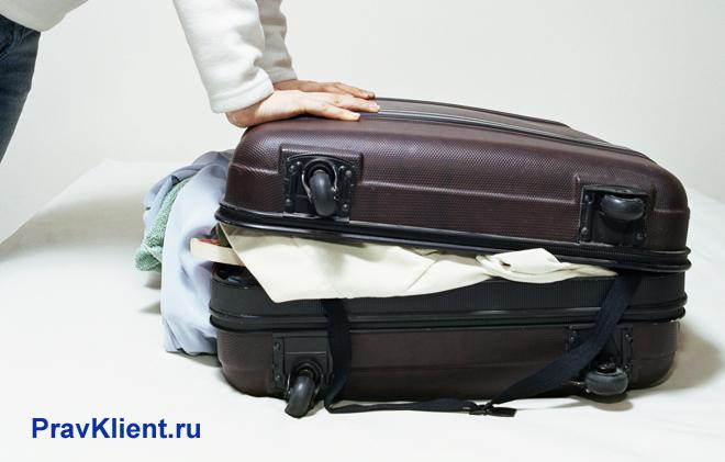 Женщина пытается закрыть чемодан