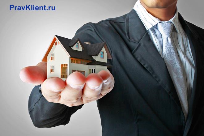 Бизнесмен держит в руке игрушечный домик