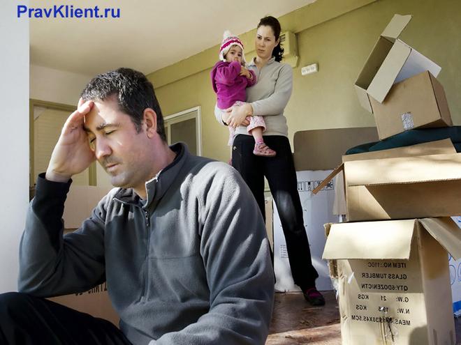 Мужчина сидит рядом с собранными вещами, сзади стоит девушка с ребенком