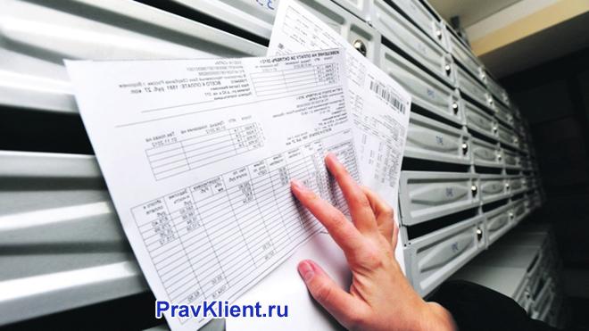 Девушка рассматривает платежки рядом с почтовыми ящиками